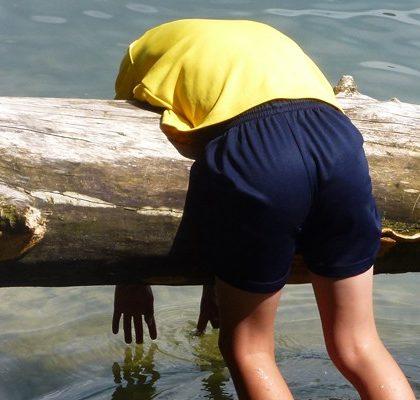 Ein Mann hängt schlapp über Baumstamm