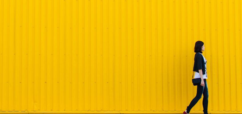 Frau geht vor gelber Hauswand vorbei