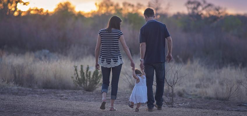 Eltern gehen mit Kind am Arm spazieren