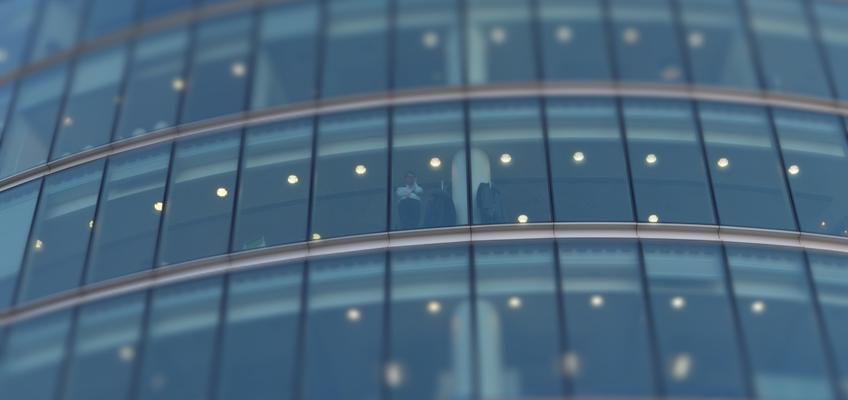 Mann schaut aus Bürogebäude runter