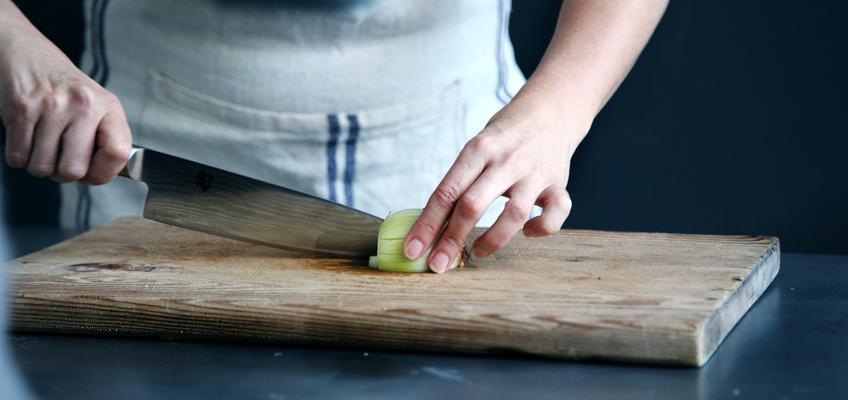 Frau schneidet Zwiebel auf Brett