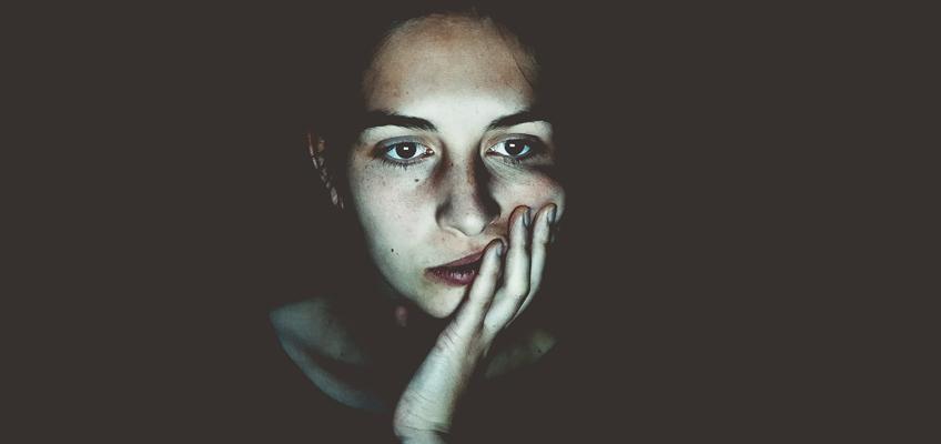 Frau sitzt nur vom Rechnerlicht beleuchtet vor Monitor