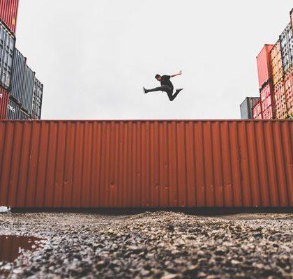 Mann spring über Transportcontainer