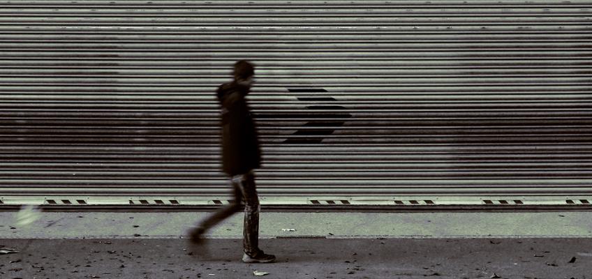 Mann geht an geschlossenem Ladengitter vorbeit