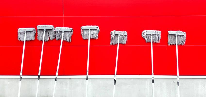 Mehrere Schrubber lehnen an roter Wand