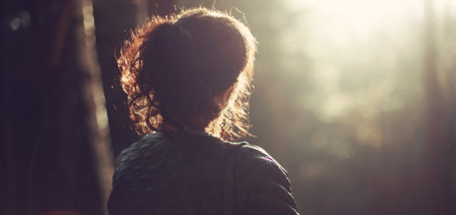 Frau steht im Wald auf Lichtung