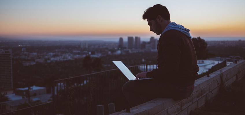 Mann sitzt mit Laptop auf dem Schop auf Mauervorsprung