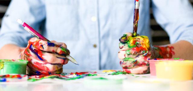 Mann sitzt mit Farbe beschmierten Händen am Tisch