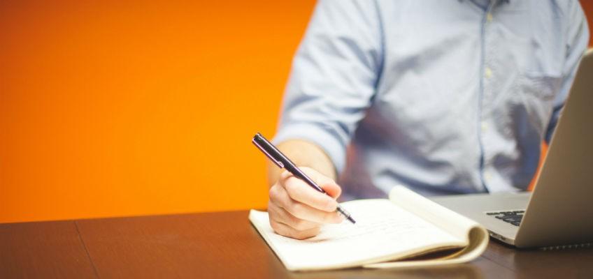 Mann schreibt etwas in Notizbuch