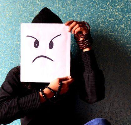 Frau hält Papier mit bösem Emoji vor Gesicht