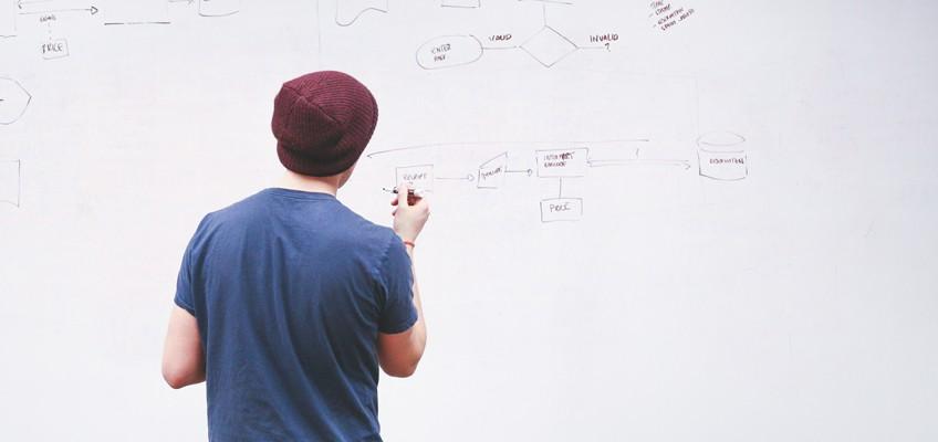Mann schreibt auf Whiteboard
