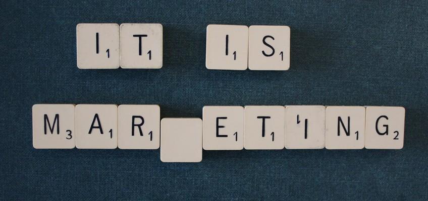 Schriftzug It is Marketing aus Scrabble-Steine