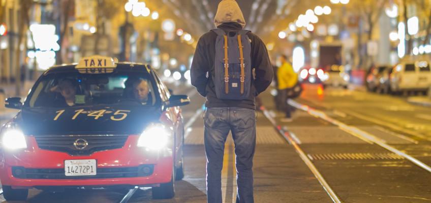 Mann mit Rucksack steht auf Fahrbahn