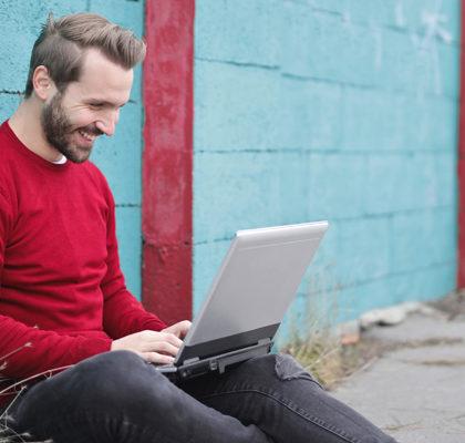 Mann sitzt mit Laptop auf Schoß auf dem Boden