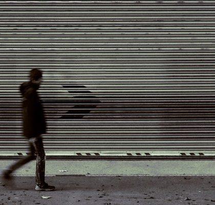 Mann geht an geschlossenen Läden vorbei