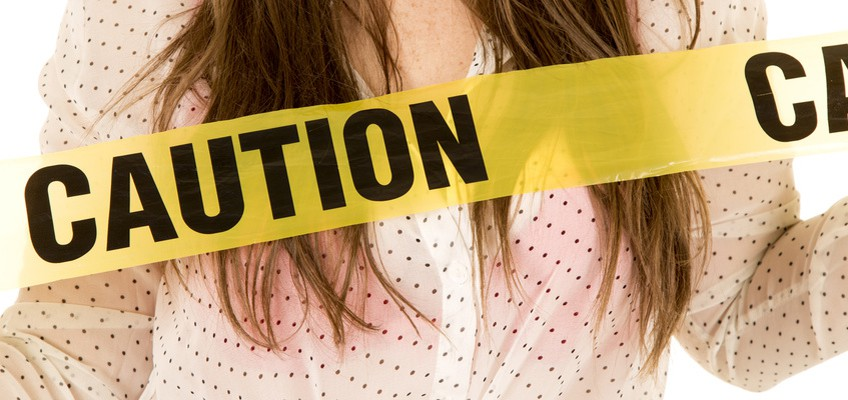 Frau hält sich Absperrband mit Schriftzug Caution vor Brust