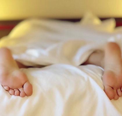 Person liegt bäuchlings auf dem Bett
