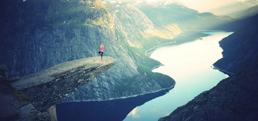Frau steht auf Felsvorsprung