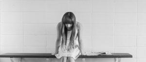 Trauriges Mädchen sitzt auf Bank