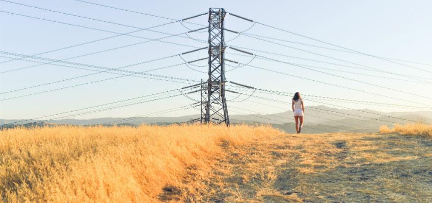 Frau auf Feld unter Strommast