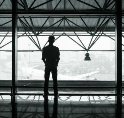 Mann schaut auf Flughafenrollfeld