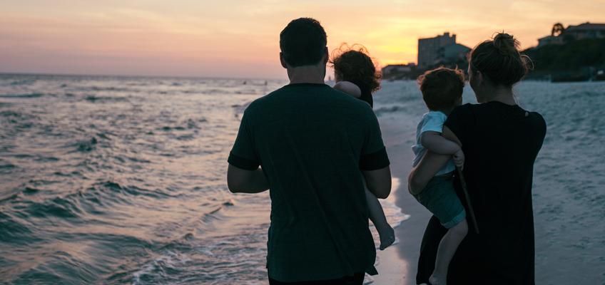 Mann und Frau mit Kindern auf dem Arm am Strand