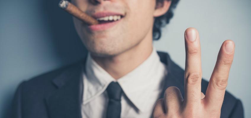 Mann mit Zigarre im Mund macht Victory-Zeichen