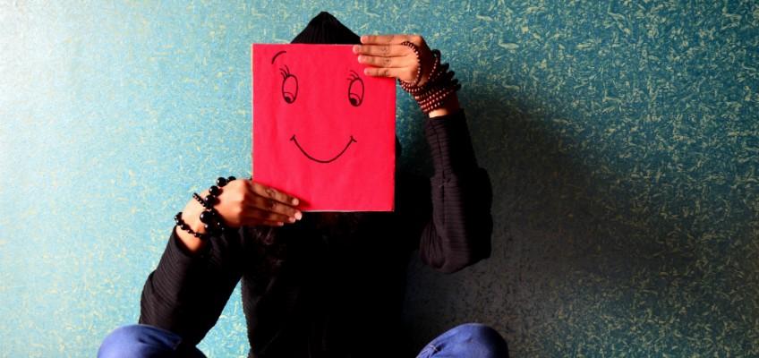 Frau hält sich Bild mit lachendem Smiley vor Gesicht