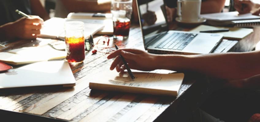 Person mit Notizblock und Laptop am Tisch