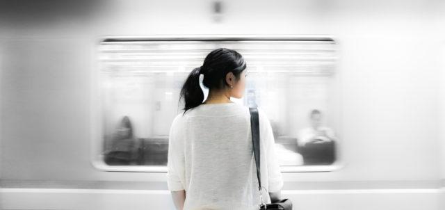 Frau steht vor vorbeifahrendem Zug