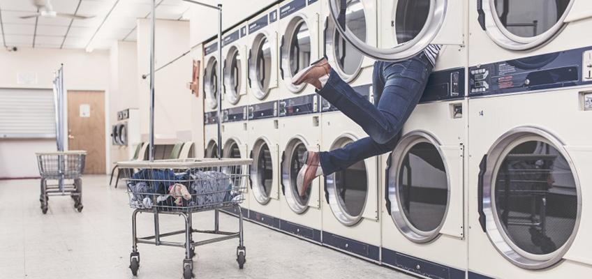 Frau hängt Kopfüber in Waschmaschinentrommel