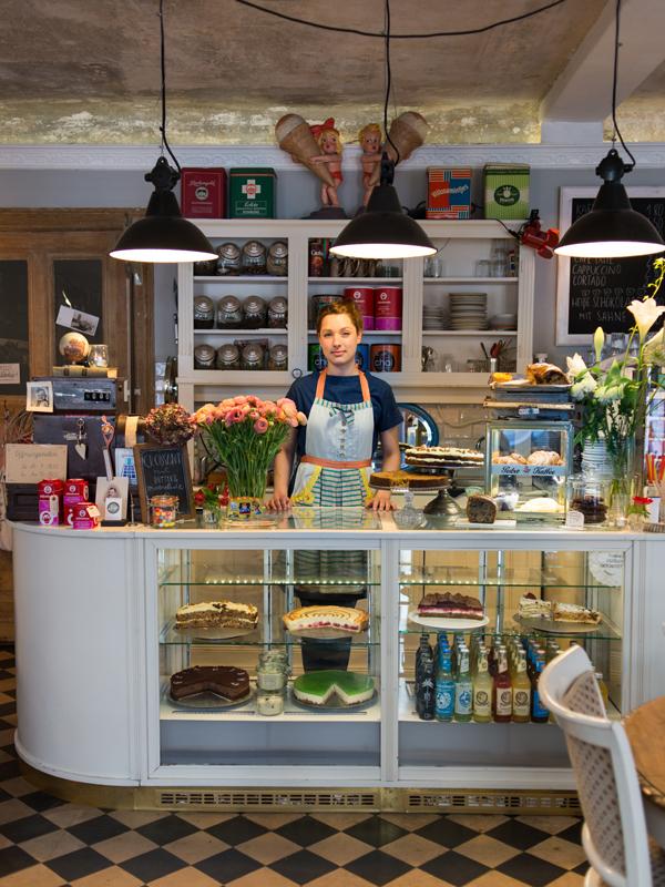 """Anne Hinkel (Café eliza, Berlin): Namenspatin fürs eliza war Eliza Doolittle aus dem Musical """"My Fair Lady"""", weil sie wie Anne Blumen liebt. Anne hat sich daran gewöhnt, dass manche Gäste sie daher """"Eliza"""" rufen."""