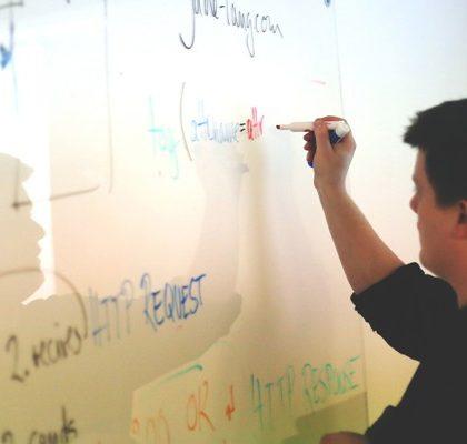 Mann schreibt an Whiteboard