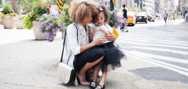 Frau hockt mit ihrer Tochter auf dem Schoß am Straßenrand
