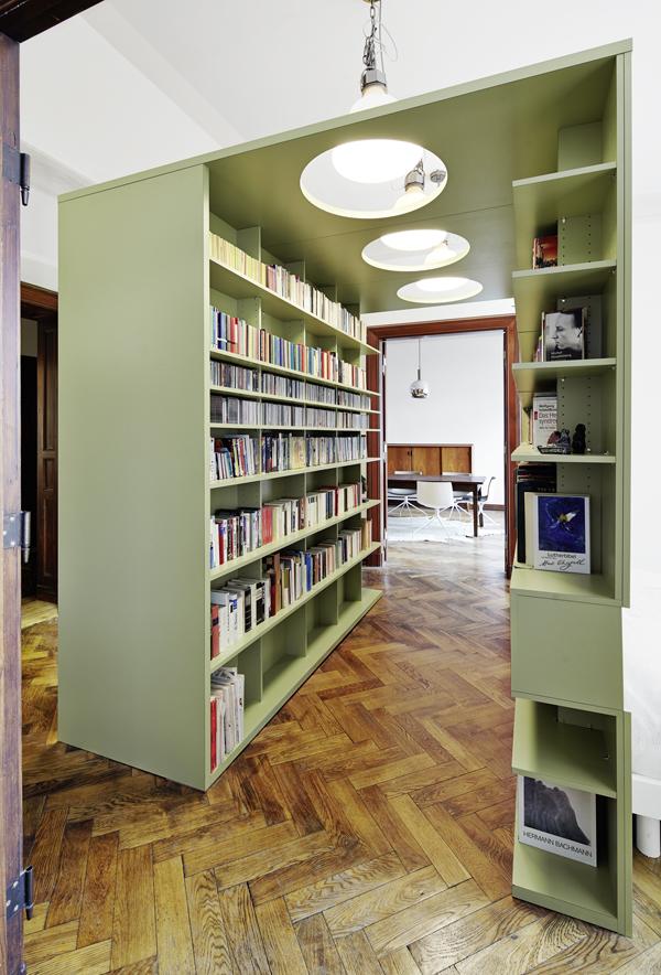Ein Büchertunnel verbindet jetzt Speise und Arbeitszimmer und blendet gleichzeitig das Bett aus, das optimal mit Licht und Sicht versorgt wird, während die Bücher – wie es sich gehört – gut geordnet und schattig in Regalen stehen.