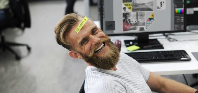 Mann mit einem Post-it auf der Stirn, auf dem Be Happy steht