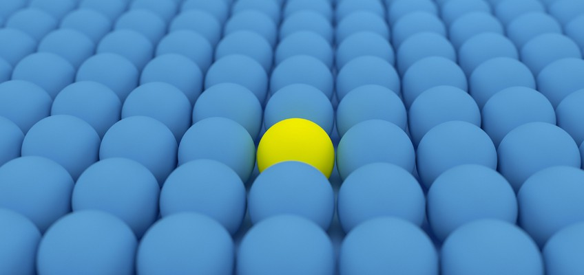 gelber Ball in Menge blauer Bälle