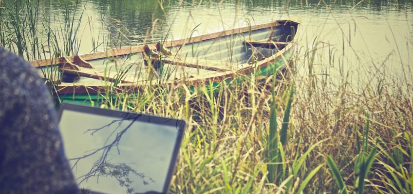 Mann am Ufer mit Laptop