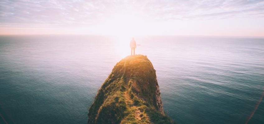 Mann steht auf hohem Felsen