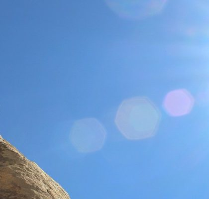 Frau klettert Felswand hinauf