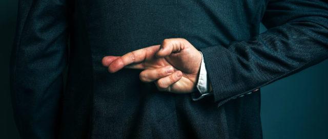 Mann mit gekreuzten Fingern auf dem Rücken