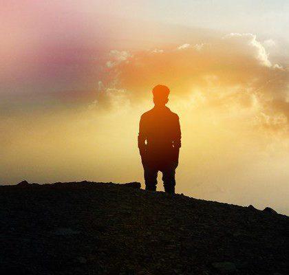 Mann schaut auf dem Berg stehend in den Sonnenuntergang