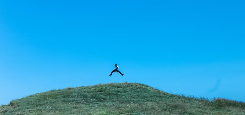 Mann macht Luftsprung auf Hügel