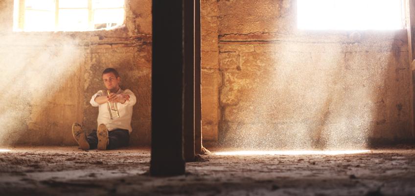 Mann sitzt auf Boden
