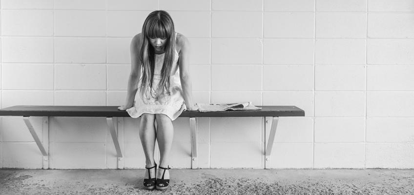 Frau sitzt traurig auf einer Bank