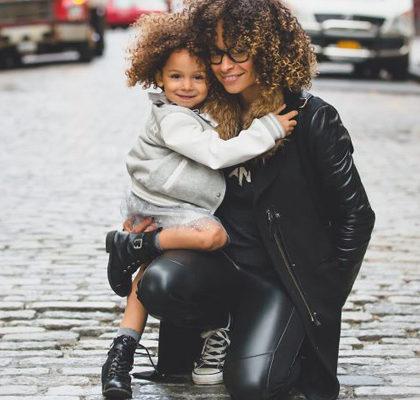 Frau hockt mit ihrer Tochter auf dem Schoß auf der Straße