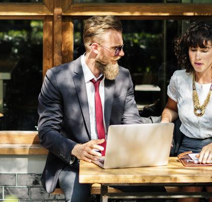 Mann und Frau sitzen mit Arbeitsunterlagen im Cafe