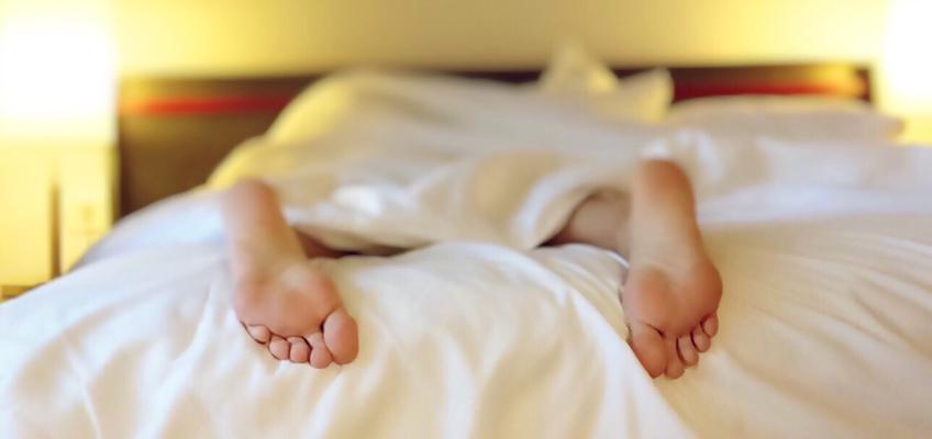 Person liegt erschöpft auf Bett