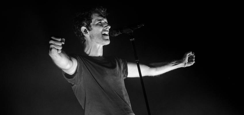 Mann breitet auf Bühne Arme aus