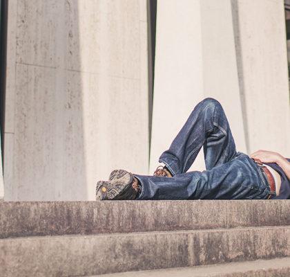 Mann liegt erschöpft auf Treppe